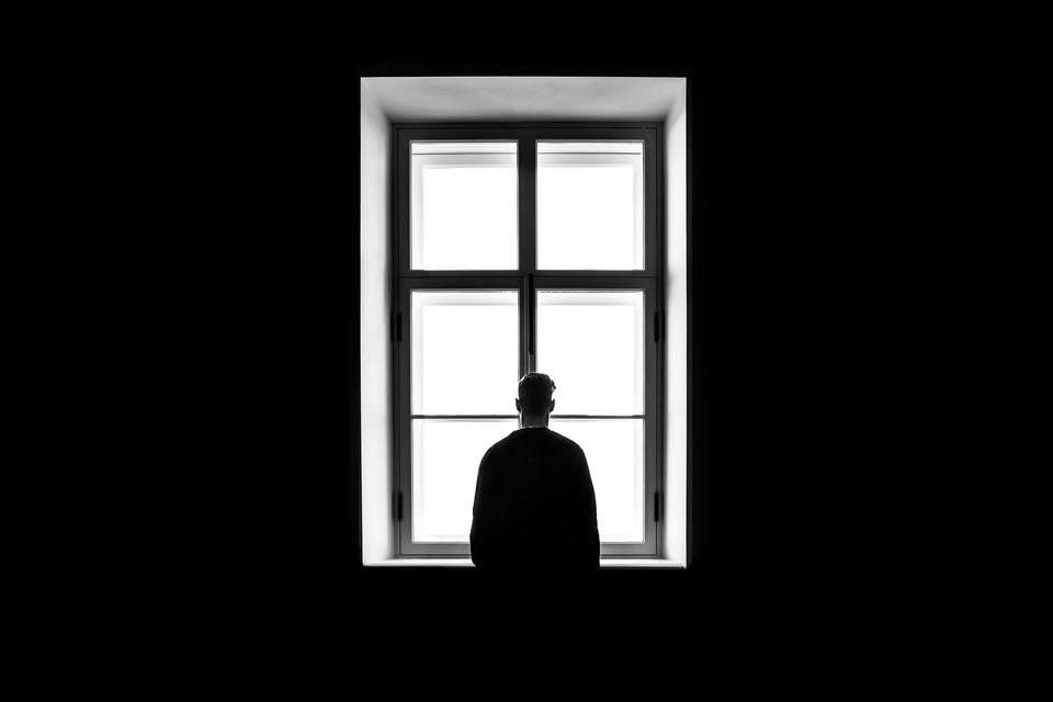 連絡がこない彼女のことを窓辺で待つ男性